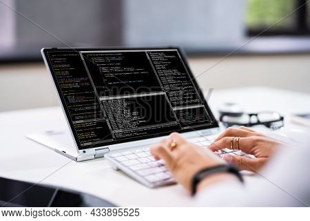 Programmer Or Coder At Office Desk Using Laptop