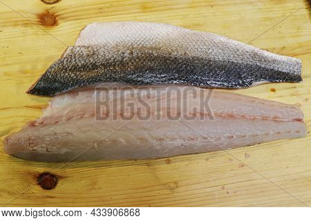 Fresh Atlantic Sea Bass Fish Fillet On A Wooden Board In Close Up