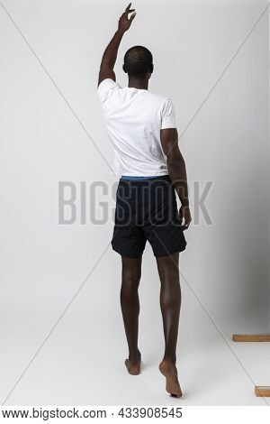 African boy turned from his back indicates a point in the void with the finger of his hand. White background