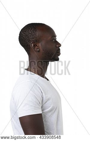 African boy in profile on a white background looks straight ahead. Copy space