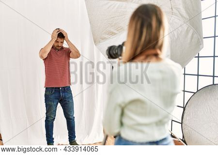 Woman photographer talking pictures of man posing as model at photography studio suffering from headache desperate and stressed because pain and migraine. hands on head.