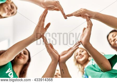 Group of young volunteers woman smiling happy make heart symbol with hands together at charity center.