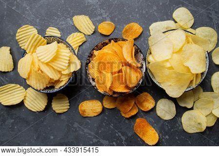 Potato chips or crisps, popular salty snack served in bowl