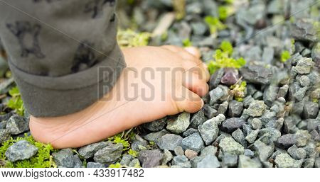 Close Up Of The One Bare Foot Of The Child Walking On Over Gravel And Copy Space.
