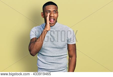 Young black man wearing casual t shirt shouting and screaming loud to side with hand on mouth. communication concept.