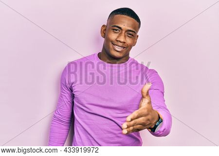 Young black man wearing casual pink sweater smiling friendly offering handshake as greeting and welcoming. successful business.