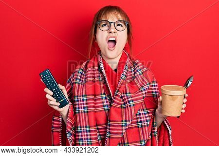 Redhead young woman wrapped in a red warm red blanket eating icecream and watching tv angry and mad screaming frustrated and furious, shouting with anger looking up.