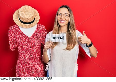 Beautiful hispanic woman holding open shopping business banner smiling happy and positive, thumb up doing excellent and approval sign