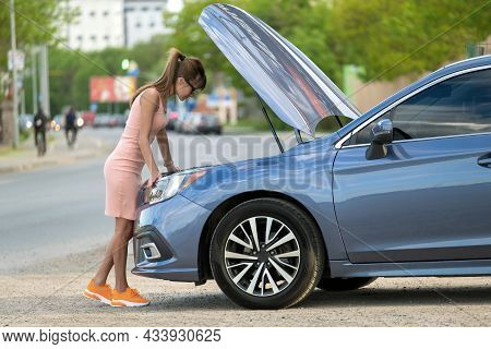 Helpless Woman Standing Near Her Car With Open Bonnet Inspecting Broken Motor. Young Female Driver H
