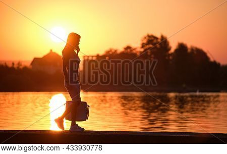 Lonely Young Woman Walking Alone On Lake Shore Enjoying Warm Evening. Wellbeing And Relaxing In Natu