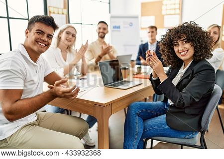 Group of young business workers clapping and looking to the camera at the office.