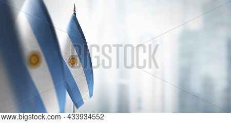 Small Flags Of Argentina On A Blurry Background Of The City