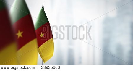 Small Flags Of Cameroon On A Blurry Background Of The City