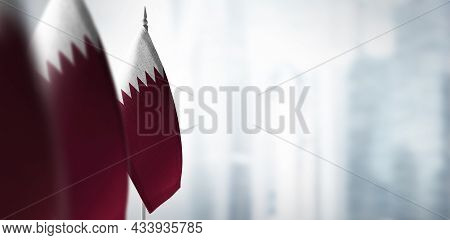 Small Flags Of Qatar On A Blurry Background Of The City