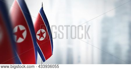 Small Flags Of North Korea On A Blurry Background Of The City