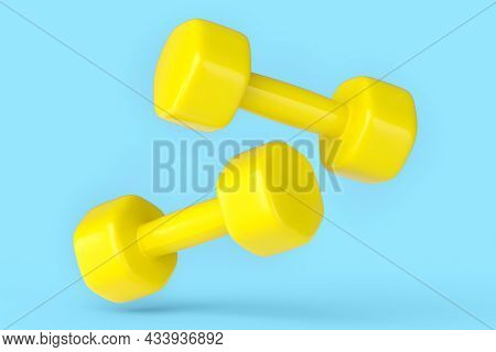Pair Of Rubber Yellow Dumbbells Isolated On Blue Background