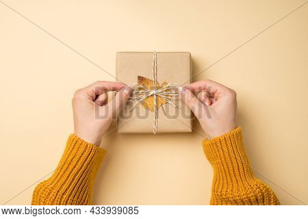 First Person Top View Photo Of Hands In Yellow Pullover Tying Twine Bow On Craft Paper Giftbox With
