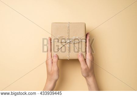 First Person Top View Photo Of Female Hands Holding Craft Paper Gift Box With Twine Bow On Isolated