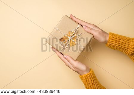 First Person Top View Photo Of Hands In Yellow Sweater Holding Craft Paper Giftbox With Twine Bow An