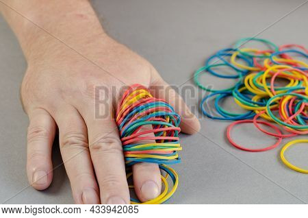 One Mans Arm And Stationery Rubber Bands On A Gray Background. Multicolored Round Rubber Bands Strun