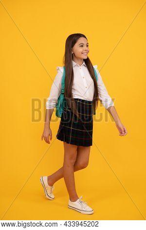 Happy Teen Girl In School Uniform Full Length On Yellow Background Making Step Forward, School.