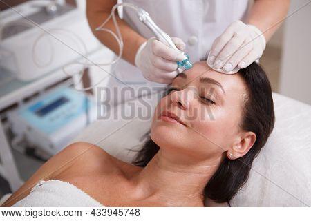Mature Woman Enjoying Getting Hydra Facial Pore Cleanse By Beautician