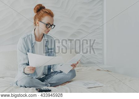 Young Concentrated Woman Housewife In Spectacles Managing Family Budget While Sitting On Bed At Home
