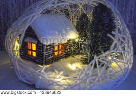 Christmas Composition In The Form Of An Artificial Wooden House With Snow On The Roof And Light From