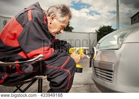 Man In Overall Working With Drill On Damage Of His Car Directly On Street
