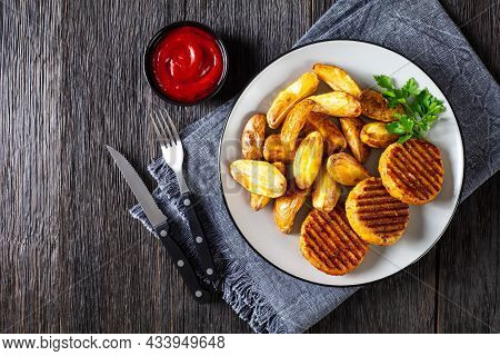 Grilled Fish Burgers With Baked Potato Wedges On A Plate With Cutlery, Flat Lay