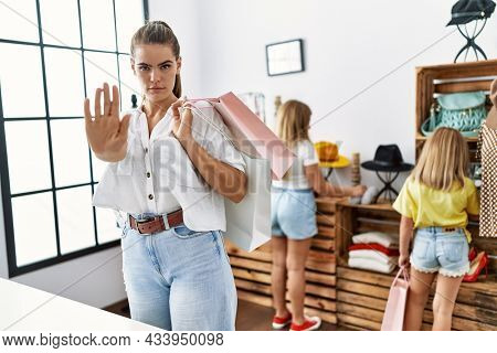 Young beautiful woman with two daughters holding shopping bags at retail shop with open hand doing stop sign with serious and confident expression, defense gesture