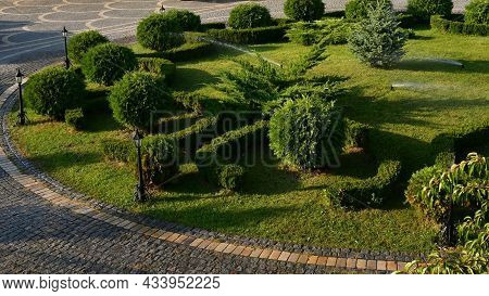 Landscaped Garden Watering Ball Shaped Mowed Shrubs At Round Lawn With Retro Lantern Streetlights. O
