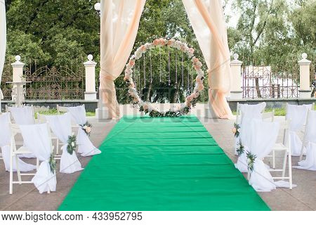 Round Wedding Arch For The Wedding Ceremony With Flowers And Crystal Pendants With A Green Carpet Fo