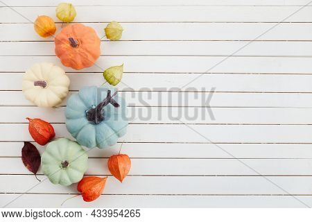 Festive Autumn Decor With Pumpkins, Chinese Latern Plants And Leaves On A White Wooden Background. C