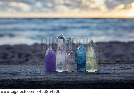 Healing Reiki Crystasls On Wood With Sea At Sunset Background. Healing Stones At The Seaside.