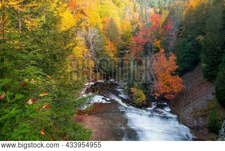Bright fall foliage at Laughing whitefish water falls state park in Michigan upper peninsula