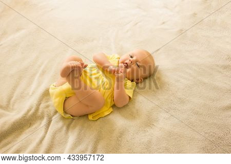 Cute, Sweet And Charming Little Girl In A Yellow Bodysuit Lying On The Bed And Smiling.