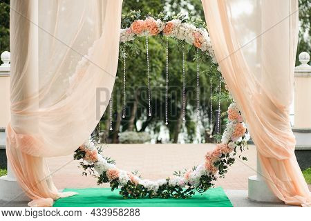 Round Wedding Arch For The Wedding Ceremony Is Decorated With Flowers And Crystal Pendants. Traditio