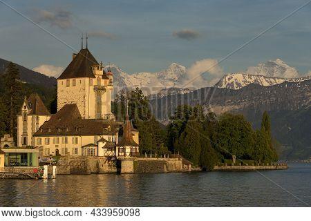 Oberhofen, Switzerland - June 01, 2019: Oberhofen Castle Looking Out Lake Thun At Sunset. Snowcapped