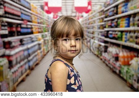 A Little Girl In A Summer Dress On A Blurry Background In A Supermarket. Concept: A Child Got Lost I