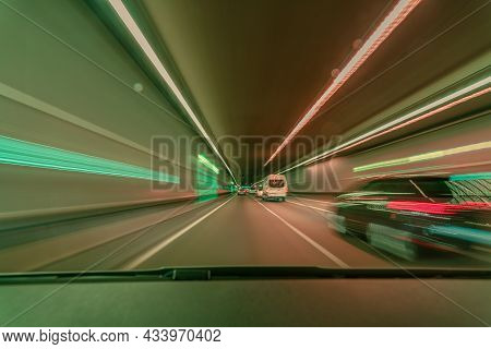 Highspeed Blurred Background, Driving Fast Through A Tunnel Overtaking A Car With Light Blurry Long