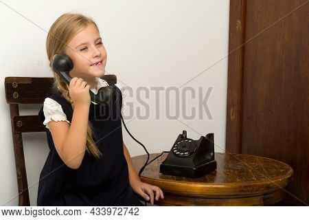 Cute Blonde Girl Talking On Vintage Telephone. Adorable Girl Of Six Or Seven Years Old Sitting On Wo
