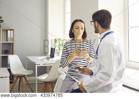 Worried Middle-aged Female Patient Explains Symptoms To Her Doctor And Complains Of Heart Pain.