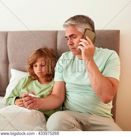 Narrow Vertical Shot Of Caring Dad Help Unhealthy Son With Fever Measure High Temperature Call For D