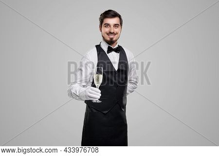Handsome Young Bearded Waiter In Elegant Uniform Offering Glass Of Champagne And Looking At Camera A
