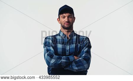 Workman In Cap And Overalls Standing With Crossed Arms Isolated On White