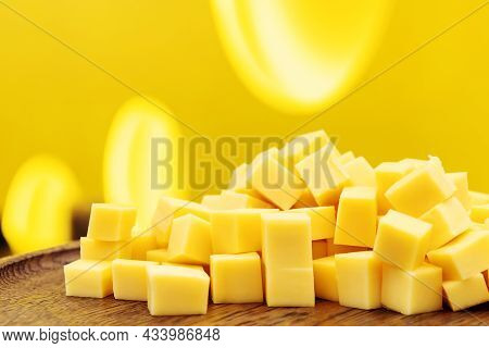 Cheese Cubes On A Yellow Background. Dairy Delicacies On A Wooden Plate. Side View