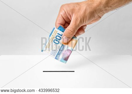 Investment concept - male hand putting 100 Swiss francs money into donation box