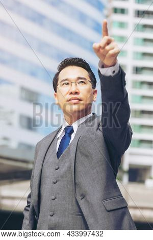 Asian Business Man Wearing A Suit  Pointing His Finger Forward On Business District , Show Commitmen