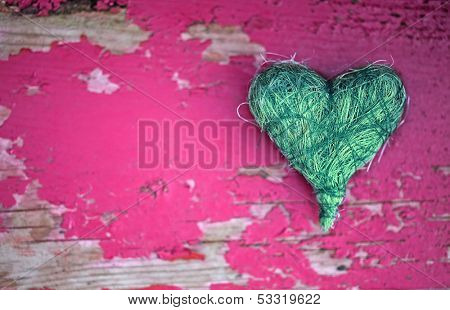 Green heart on pink wooden background
